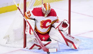 Calgary Flames goaltender David Rittich (33) makes a save on a shot from Ottawa Senators left wing Tim Stutzle, not shown, during the second period of an NHL game in Ottawa, Ontario, on Saturday, Feb. 27, 2021. (Sean Kilpatrick/The Canadian Press via AP)