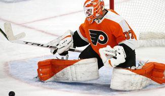 Philadelphia Flyers goalie Brian Elliott (37) makes a pad save during the third period of an NHL hockey game against the Buffalo Sabres, Saturday, Feb. 27, 2021, in Buffalo, N.Y. (AP Photo/Jeffrey T. Barnes)