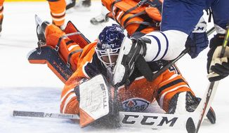 Edmonton Oilers goalie Mike Smith (41) makes the save as he is hit with a skate from a Toronto Maple Leafs player during the first period of an NHL game in Edmonton, Alberta, on Saturday, Feb. 27, 2021. (Jason Franson/The Canadian Press via AP)
