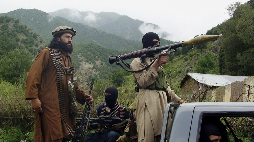 FILE - In this Aug. 5, 2012, file photo, Pakistani Taliban patrol in their stronghold of Shawal in Pakistani tribal region of South Waziristan. Militant attacks are on the rise in Pakistan amid a growing religiosity that has brought greater intolerance, prompting one expert to voice concern the country could be overwhelmed by religious extremism. (AP Photo/Ishtiaq Mahsud, File)