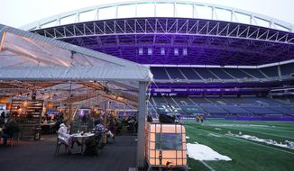 "People eat dinner in an outdoor dining tent set up at Lumen Field, the home of the Seattle Seahawks NFL football team, Thursday, Feb. 18, 2021, in Seattle. The ""Field To Table"" event was the first night of several weeks of dates that offer four-course meals cooked by local chefs and served on the field at tables socially distanced as a precaution against the COVID-19 pandemic, which has severely limited options for dining out at restaurants in the area. (AP Photo/Ted S. Warren)"