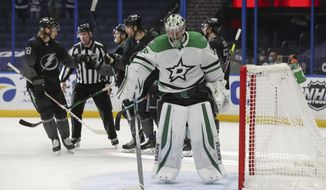 Dallas Stars goaltender Anton Khudobin stands in front of the goal as Tampa Bay Lightning players celebrate a goal during the second period of an NHL hockey game Saturday, Feb. 27, 2021, in Tampa, Fla. (AP Photo/Mike Carlson)