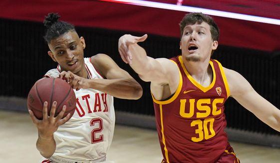 Utah guard Ian Martinez (2) pulls down a rebound as Southern California guard Noah Baumann (30) defends during the first half of an NCAA college basketball game Saturday, Feb. 27, 2021, in Salt Lake City. (AP Photo/Rick Bowmer) **FILE**