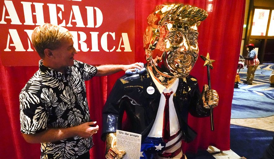 Sculptor Tommy Zegan, polishes his statue of former president Donald Trump on display at the Conservative Political Action Conference (CPAC) Friday, Feb. 26, 2021, in Orlando, Fla. Zegan says he has to wipe finger prints off the statue every hour or so. (AP Photo/John Raoux)