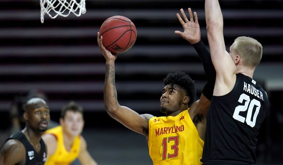 Maryland guard Hakim Hart (13) goes up for a shot against Michigan State forward Joey Hauser (20) during the first half of an NCAA college basketball game, Sunday, Feb. 28, 2021, in College Park, Md. (AP Photo/Julio Cortez)