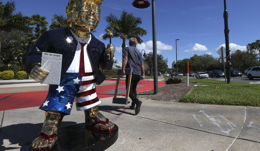Tommy Zegan walks away after moving his golden Donald Trump statue across the street from CPAC at the Hyatt Regency in Orlando, Fla on Sunday, Feb. 28, 2021. (Sam Thomas/Orlando Sentinel via AP)