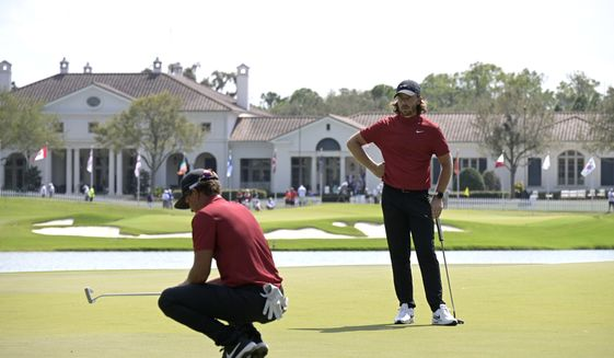 Tommy Fleetwood, right, of England, watches as Cameron Champ lines up a putt on the 10th green during the final round of the Workday Championship golf tournament Sunday, Feb. 28, 2021, in Bradenton, Fla. Both are wearing clothing honoring Tiger Woods. (AP Photo/Phelan M. Ebenhack)