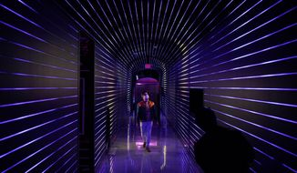 Corvas Brinkerhoff, co-founder of Meow Wolf and creative director of Omega Mart, walks through Omega Mart, an immersive art installation by arts production company Meow Wolf, Thursday, Feb. 18, 2021, in Las Vegas. The installation is located at Area15, a retail and entertainment complex in Las Vegas. (AP Photo/John Locher)