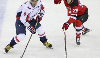 Washington Capitals left wing Alex Ovechkin (8) moves the puck as New Jersey Devils defenseman Damon Severson (28) defends during the first period of an NHL hockey game Sunday, Feb. 28, 2021, in Newark, N.J. (Andrew Mills/NJ Advance Media via AP)