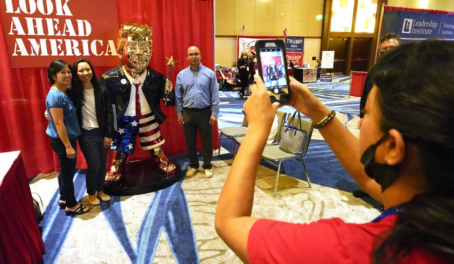 Conference attendees pose for a photo next to a statue of former president Donald Trump at the merchandise show at the Conservative Political Action Conference (CPAC) Saturday, Feb. 27, 2021, in Orlando, Fla. (AP Photo/John Raoux)