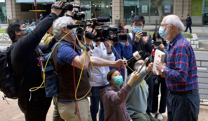 John Clancey, right, an American lawyer who became the first foreigner arrested under Hong Kong's national security law, displays a book before appearing at a police station in Hong Kong Sunday, Feb. 28, 2021. Clancey appeared at a police station Sunday, following a surprise request from police Friday. (AP Photo/Vincent Yu)