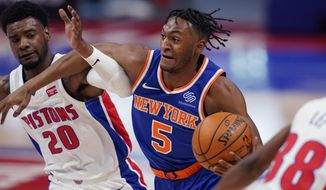 New York Knicks guard Immanuel Quickley (5) drives as Detroit Pistons guard Josh Jackson (20) defends during the first half of an NBA basketball game, Sunday, Feb. 28, 2021, in Detroit. (AP Photo/Carlos Osorio)