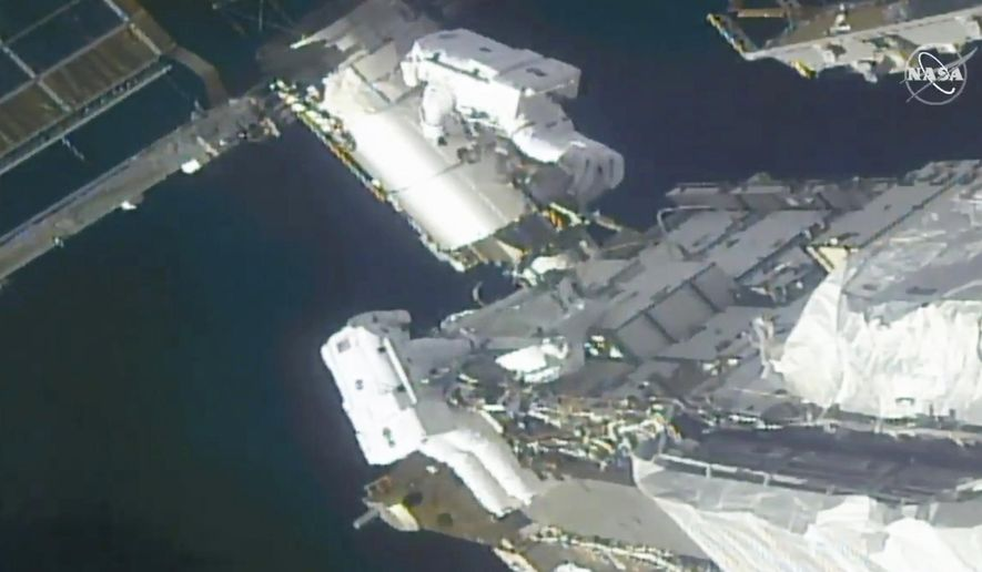 In this image taken from NASA video, NASA astronauts Kate Rubins, top, and Victor Glover work outside the International Space Station Sunday, Feb. 28, 2021. Thespacewalking astronauts ventured out Sunday to install support frames for new, high-efficiency solar panels arriving at the International Space Station later this year.  (NASA via AP)