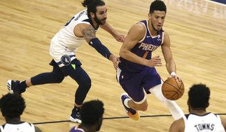 Phoenix Suns' Devin Booker (1) drives the ball past Minnesota Timberwolves' Ricky Rubio (9) in the first half of an NBA basketball game, Sunday, Feb. 28, 2021, in Minneapolis. (AP Photo/Stacy Bengs)