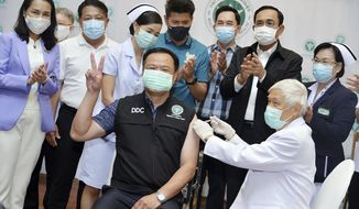 In this photo released by Government Spokesman Office, Thailand's Prime Minister Prayuth Chan-ocha, second right in the background, claps his hands after Thailand's Public Health Minister Anutin Charnvirakul received the first China's Sinovac vaccine at Bamrasnaradura Hospital in Bangkok, Thailand, Sunday, Feb. 28 , 2021. (Government Spokesman Office via AP)