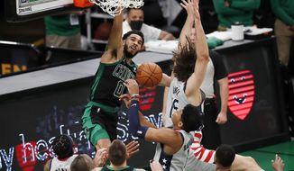 Boston Celtics' Jayson Tatum (0) dunks against Washington Wizards' Robin Lopez (15) during the first half of an NBA basketball game, Sunday, Feb. 28, 2021, in Boston. (AP Photo/Michael Dwyer)