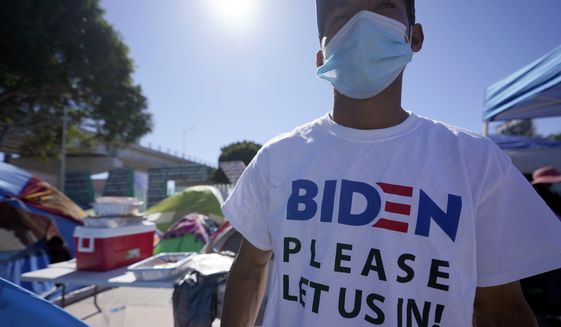 """A Honduran man seeking asylum in the United States wears a shirt that reads, """"Biden please let us in,"""" as he stands among tents that line an entrance to the border crossing, Monday, March 1, 2021, in Tijuana, Mexico. (AP Photo/Gregory Bull)"""