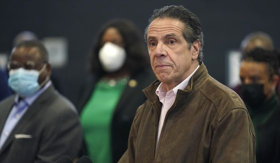 In this Feb. 22, 2021, photo, New York Gov. Andrew Cuomo, right, pauses to listen to a reporter's question during a news conference at a COVID-19 vaccination site in the Brooklyn borough of New York. New York's attorney general said she's moving forward with an investigation into sexual harassment allegations against the governor after receiving a letter from his office Monday authorizing her to take charge of the probe. (AP Photo/Seth Wenig, Pool, file)