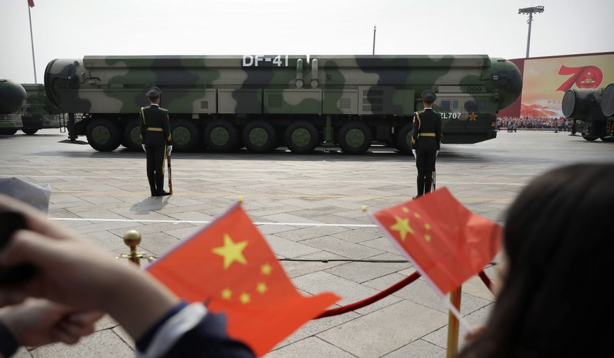In this Oct. 1, 2019, file photo spectators wave Chinese flags as military vehicles carrying DF-41 ballistic missiles roll during a parade to commemorate the 70th anniversary of the founding of Communist China in Beijing. (AP Photo/Mark Schiefelbein) **FILE**