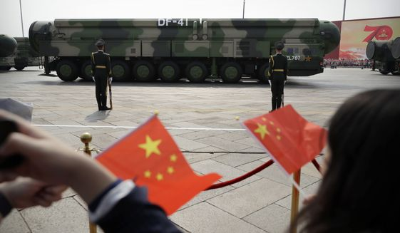 In this Oct. 1, 2019, file photo, spectators wave Chinese flags as military vehicles carrying DF-41 ballistic missiles roll during a parade to commemorate the 70th anniversary of the founding of Communist China in Beijing. (AP Photo/Mark Schiefelbein) ** FILE **