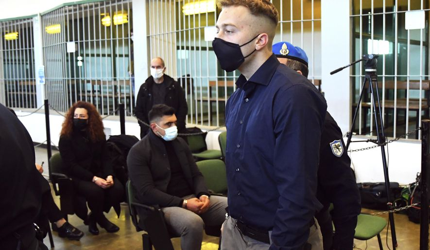 Finnegan Lee Elder, from the United States, walks past to Rosa Maria Esilio, widow of slain Carabinieri military police officer Mario Cerciello Rega, background left, and Paolo Cerciello Rega, brother of Mario, center, prior to a hearing in the trial where he and Gabriel Natale-Hjorth are accused of slaying a plainclothes Carabinieri officer while on vacation in Italy in July 2019, in Rome, Monday, March 1, 2021.    (Alberto Pizzoli/Pool Photo via AP)