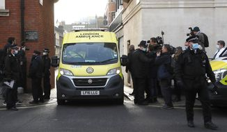 Police officers stand at an entrance to the King Edward VII Hospital where Prince Philip is being treated for an infection, as an ambulance is driven out, in London, Monday, March 1, 2021. (AP Photo/Frank Augstein)