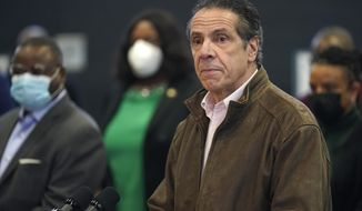 In this Feb. 22, 2021 photo, New York Gov. Andrew Cuomo, right, pauses to listen to a reporter's question during a news conference at a COVID-19 vaccination site in the Brooklyn borough of New York. New York's attorney general said she's moving forward with an investigation into sexual harassment allegations against the governor after receiving a letter from his office Monday authorizing her to take charge of the probe. (AP Photo/Seth Wenig, Pool, file)  **FILE**