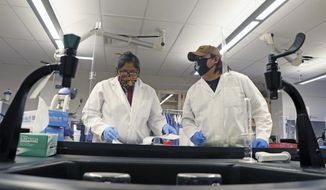 This undated image provided by Navajo Technical University shows Robinson Tom, right, assisting general education graduate Noelle Clark with a biology assignment at the university in Crownpoint, New Mexico. Tom worked as a lab assistant in the NTU Wet Labs upon graduation in May 2020. (Daniel Vandever, NTU, via AP)