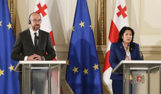 In this photo provided by the Georgian Presidential Press Office, Georgia's President Salome Zurabishvili, right, speaks during a joint news briefing with European Council President Charles Michel in Tbilisi, Georgia, Monday, March 1, 2021 (Georgian Presidential Press Office via AP)