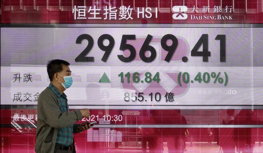 A man walks past a bank's electronic board showing the Hong Kong share index at Hong Kong Stock Exchange in Hong Kong Tuesday, March 2, 2021. Asian stock markets were mixed Tuesday after Wall Street rose as investor concern about possible higher interest rates receded. (AP Photo/Vincent Yu)