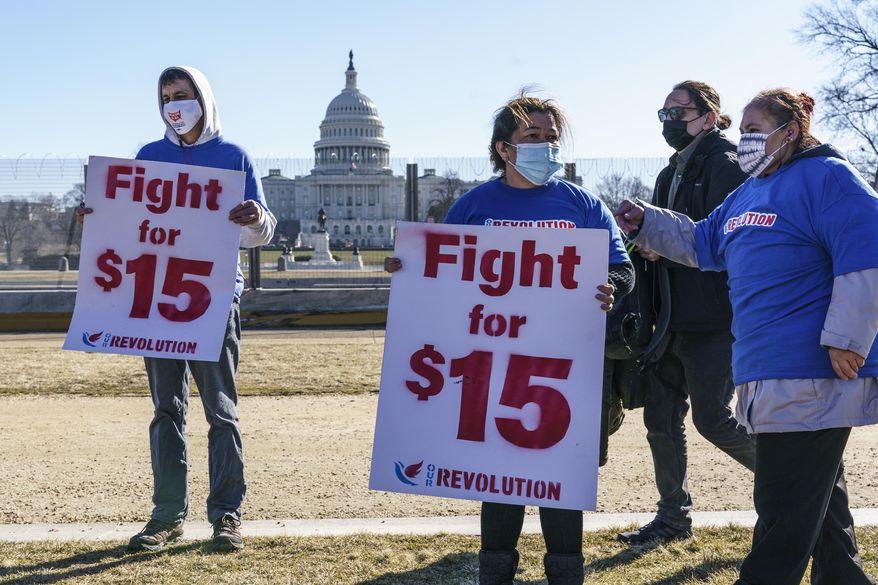 In this file photo, activists appeal for a $15 minimum wage near the Capitol in Washington, Thursday, Feb. 25, 2021. The $1.9 trillion COVID-19 relief bill being prepped in Congress includes a provision that over five years would hike the federal minimum wage to $15 an hour. (AP Photo/J. Scott Applewhite)  **FILE**