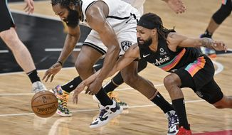 Brooklyn Nets' James Harden, left, and San Antonio Spurs' Patty Mills chase the ball during the first half of an NBA basketball game, Monday, March 1, 2021, in San Antonio. (AP Photo/Darren Abate)