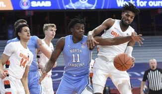 North Carolina forward Day'Ron Sharpe (11) and Syracuse forward Quincy Guerrier (1) work on getting the ball during an NCAA college basketball game in Syracuse, N.Y., Monday, March 1, 2021. (Dennis Nett/The Post-Standard via AP)