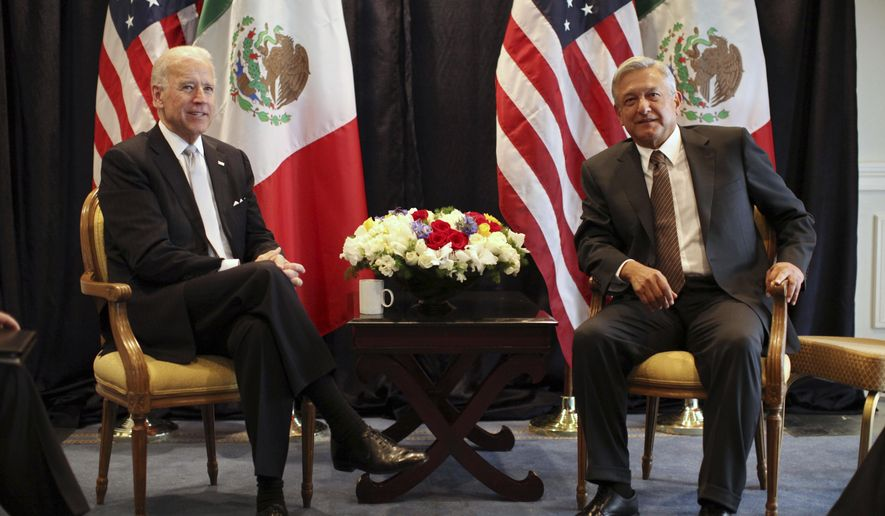 FILE - Then-U.S. Vice President Joe Biden, left, poses for photos with then-Mexican presidential candidate Andres Manuel Lopez Obrador in Mexico City, Monday March 5, 2012. President Biden is planning a virtual meeting with Mexican President Obrador. The meeting, on Monday, March 1, 2021, is a chance for the pair to talk more fully about migration, treating the coronavirus and cooperating on economic and national security issues. (AP Photo/Alexandre Meneghini, File)