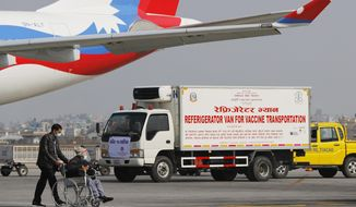 FILE- In this Jan. 21, 2021 file photo, a van stands parked waiting to transport AstraZeneca/Oxford University vaccines, manufactured under license by Serum Institute of India, at Tribhuwan International Airport in Kathmandu, Nepal. The government is negotiating with India's Serum Institute to obtain 5 million doses for the second stage of the campaign, in which 3.7 million elderly people are to be vaccinated starting this Sunday. (AP Photo/Niranjan Shrestha, File)