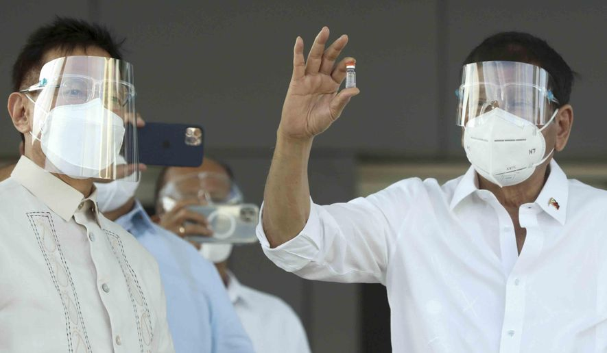 In this photo provided by the Malacanang Presidential Photographers Division, Philippine President Rodrigo Duterte, right, holds a vial containing the Sinovac vaccine from China as it arrives at the Villamor Air Base in Manila, Philippines on Sunday Feb. 28, 2021. The Philippines received its first batch of COVID-19 vaccine Sunday, among the last in Southeast Asia to secure the critical doses despite having the second-highest number of coronavirus infections and deaths in the hard-hit region. (Toto Lozano/Malacanang Presidential Photographers Division via AP)