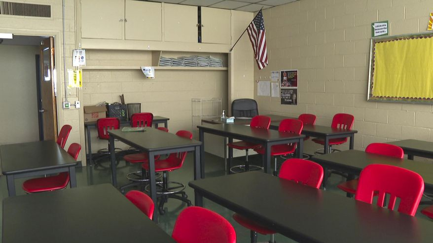 In this image made from video, an empty classroom is shown at David Ellis Academy in Detroit, Monday, Feb. 8, 2021. It's coming up on a year since most of the students at the pre-K through 8th grade public charter school last had an in-person school day. (AP Photo/Mike Householder) ** FILE **