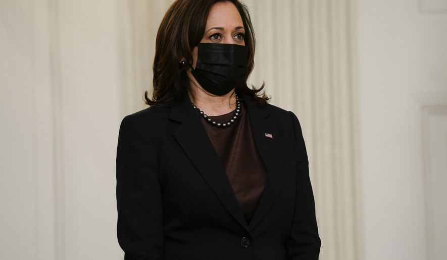 Vice President Kamala Harris listens as President Joe Biden speaks about efforts to combat COVID-19, in the State Dining Room of the White House, Tuesday, March 2, 2021, in Washington. (AP Photo/Evan Vucci)