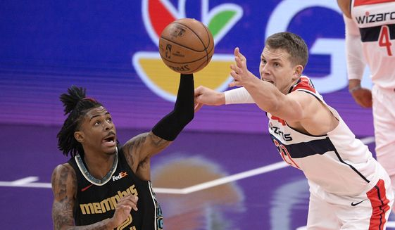 Memphis Grizzlies guard Ja Morant (12) and Washington Wizards center Moritz Wagner (21) reach for the ball during the first half of an NBA basketball game, Tuesday, March 2, 2021, in Washington. (AP Photo/Nick Wass)
