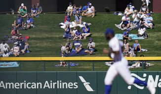 Socially distanced fans watch as Chicago Cubs right fielder Jason Heyward, foreground, head toward the dugout after the second inning of a spring baseball game against the Kansas City Royals in Mesa, Ariz., Tuesday, March 2, 2021. (AP Photo/Jae C. Hong)
