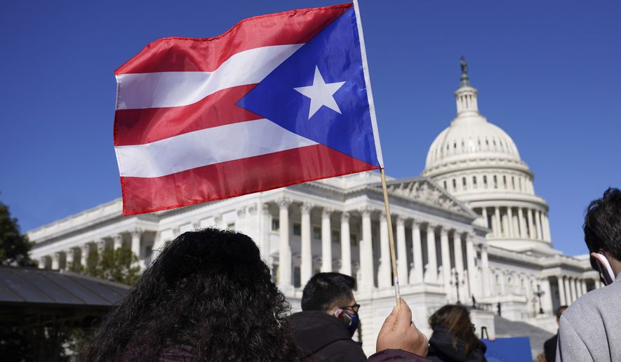 A woman waves the flag of Puerto Rico during a news conference on Puerto Rican statehood on Capitol Hill in Washington, Tuesday, March 2, 2021. (AP Photo/Patrick Semansky)