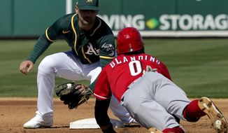 Oakland Athletics' Pete Kozma tags out Cincinnati Reds Alex Blandino (0) on a steal attempt during the first inning of a spring training baseball game, Monday, March 1, 2021, in Mesa, Ariz. (AP Photo/Matt York)