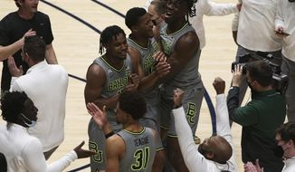 Baylor players celebrate on the court after an overtime win against West Virginia in an NCAA college basketball game Tuesday, March 2, 2021, in Morgantown, W.Va. (AP Photo/Kathleen Batten)