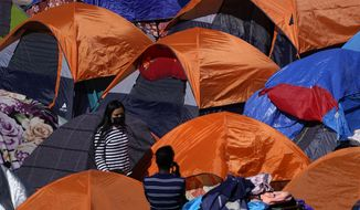 Tents used by migrants seeking asylum in the United States line an entrance to the border crossing, Monday, March 1, 2021, in Tijuana, Mexico. (AP Photo/Gregory Bull) ** FILE **