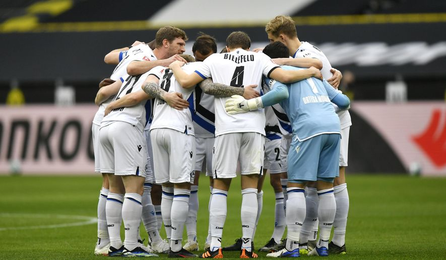 Arminia Bielefeld players gather prior to the start of the German Bundesliga soccer match between Borussia Dortmund and Arminia Bielefeld in Dortmund, Germany, Saturday, Feb. 27, 2021. (AP Photo/Martin Meissner, Pool)
