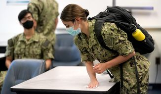 FILE - Inn this Aug. 24, 2020, file photo, a midshipman uses a sanitizing wipe to clean her desk before the start of a leadership class at the U.S. Naval Academy in Annapolis, Md. The U.S. Naval Academy is developing plans to begin vaccinating midshipmen in March 2021, so students can deploy out to ships and with Navy teams as part of their training this summer. (AP Photo/Julio Cortez, File)