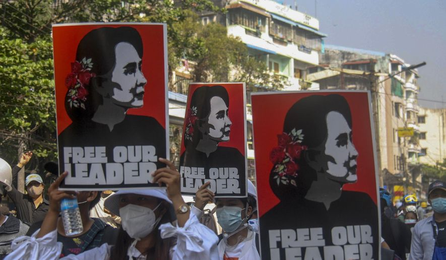 Anti-coup protesters display pictures of deposed Myanmar leader Aung San Suu Kyi in Yangon, Myanmar, Tuesday, March 2, 2021. Police in Myanmar repeatedly used tear gas and rubber bullets Tuesday against crowds protesting last month's coup, but the demonstrators regrouped after each volley and tried to defend themselves with barricades as standoffs between protesters and security forces intensified. (AP Photo)