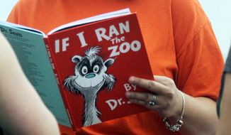 """In this Sept. 24, 2013, file photo, Courtney Keating, education coordinator of The Literacy Center in Evansville, Ind., reads """"If I Ran the Zoo,"""" By Dr. Seuss, to passersby during an event to promote literacy along the Evansville Riverfront. Dr. Seuss Enterprises, the business that preserves and protects the author and illustrator's legacy, announced on his birthday, Tuesday, March 2, 2021, that it would cease publication of several children's titles including """"And to Think That I Saw It on Mulberry Street"""" and """"If I Ran the Zoo,"""" because of insensitive and racist imagery. (Erin McCracken/Evansville Courier & Press via AP, File)"""