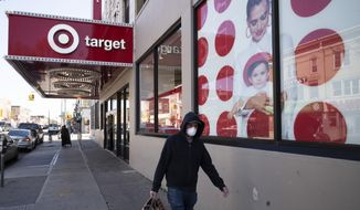 In this April 6, 2020, file photo, a customer wearing a mask carries his purchases as he leaves a Target store during the coronavirus pandemic, in the Brooklyn borough of New York. (AP Photo/Mark Lennihan, File)
