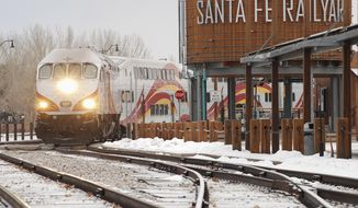 FILE - In this Jan. 14, 2019, file photo, a New Mexico Rail Runner commuter train departs from Santa Fe, N.M. New Mexico's commuter system linking metro Albuquerque with Santa Fe will resume service next Monday, March 8, 2021, after being shut down for nearly a year because of the COVID-19 pandemic. (AP Photo/Morgan Lee, File)